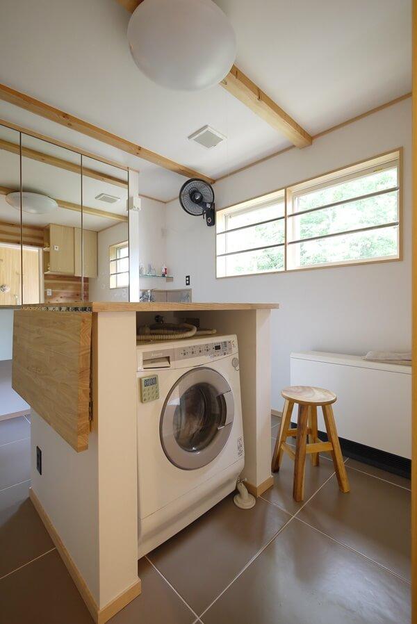 作業台の下に洗濯機を置いた洗面所