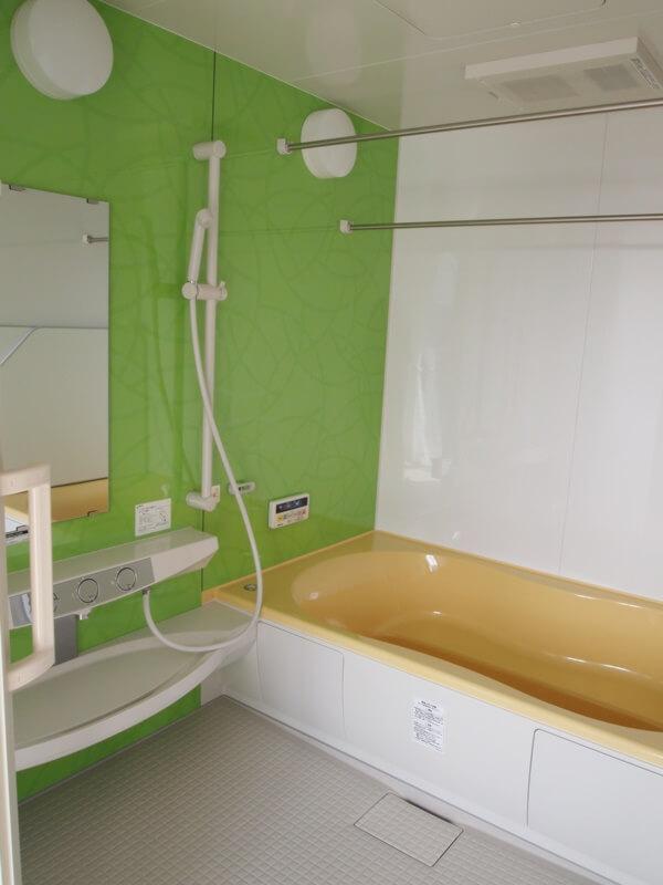 グリーンの壁、黄色い浴槽のユニットバスです