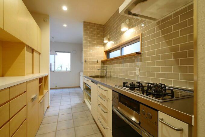 グレーのタイルの壁と、窓上のカウンターのあるキッチン