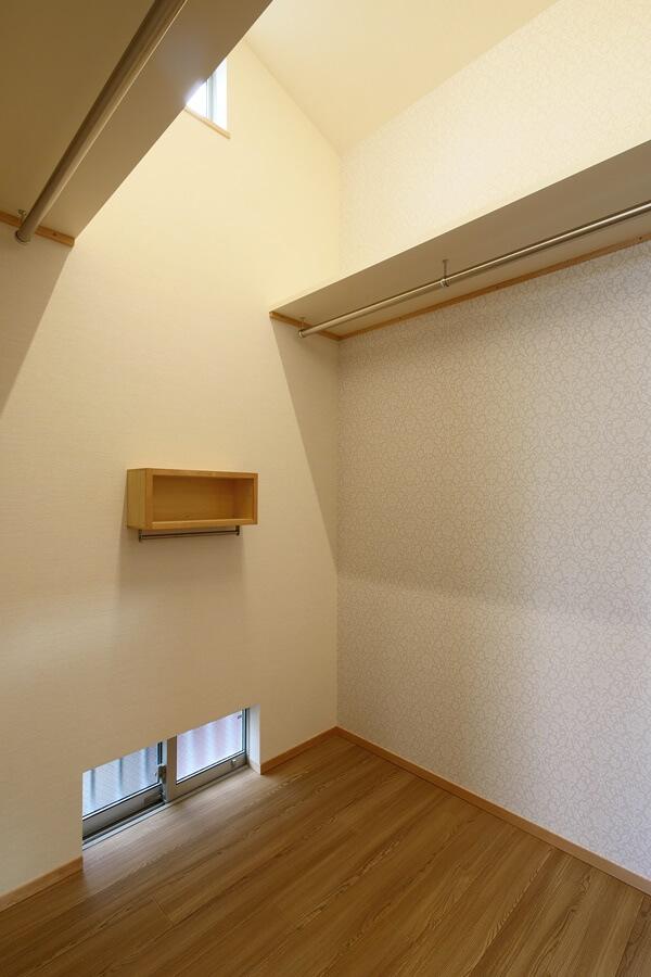 高天井のウォークインクロゼットには鏡やアクセサリーを置ける収納棚を