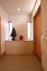 腰高の下足箱と窓の効果で広さをみせる玄関