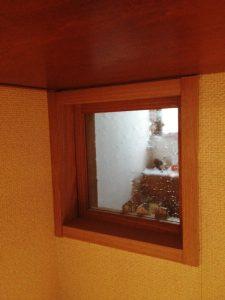 キッチン背面収納の小窓から玄関の様子が見える