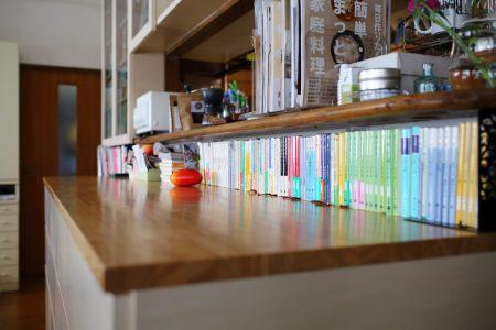 キッチンのカウンター下に文庫が並ぶデザイン