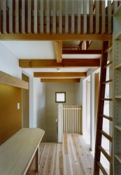個室をつなぐ階段上のスペースに共有デスクと本棚を