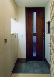 玄関収納をたっぷり設け、細いラインの縦格子の木製玄関引戸でスペースを有効に。