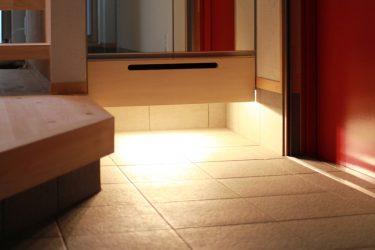 下足箱の下部は間接照明。引出は土間用のサンダル専用の収納に。