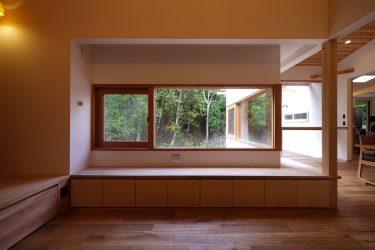 リビングの木製窓から森の景色を楽しむ