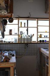 窓際の飾る収納棚とキッチンコンロ