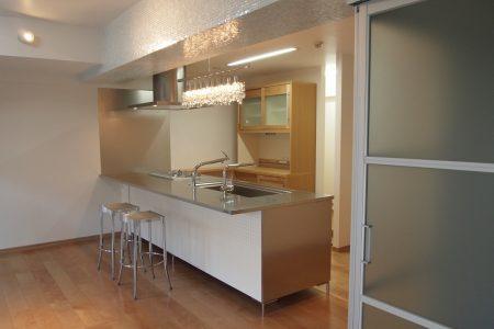 TOYOキッチンの照明、椅子を置き、ガラスモザイクタイルを梁に貼ったキッチン
