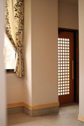 階段ホールと色違いのカーテンを設けた玄関