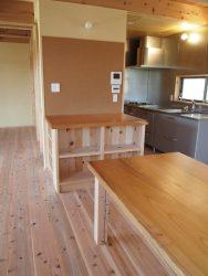 ダイニングテーブルと隣り合うコルク壁と収納