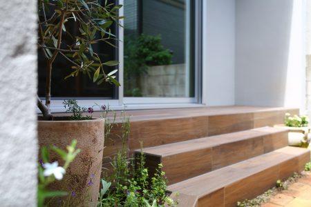 テラスは木目調のタイルで、庭の古レンガとつながるように
